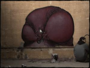 Graffiti fait à Bruxelles dans le cadre du documentaire de charline branger par l'artiste Teddy Ros, fait à la bombe spray can représentant un monstre avec une petite caméra