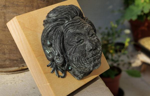"""photo de la sculpture """"Mamy Smille"""" 2019, supersculpley réaliser par l'artiste Teddy Ros avec patine bronze bleu socle bois de chêne."""